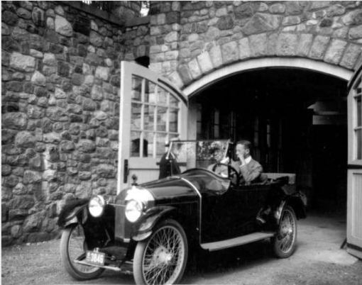 James Scripps Booth (behind the wheel) with brother Warren Scripps Booth in a Scripps-Booth 4-cylinder Model C at Tower Garage at Cranbrook House. Their father George Gough Booth stands next to the car, partially hidden by the windshield.  Circa 1917, Cranbrook Archives.