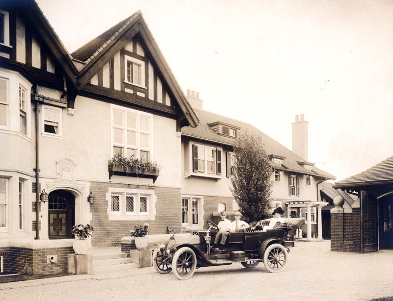 Warren and Grace Booth with chauffeur in the Chalmers 40 in front of Cranbrook House. Circa 1910, Cranbrook Archives.