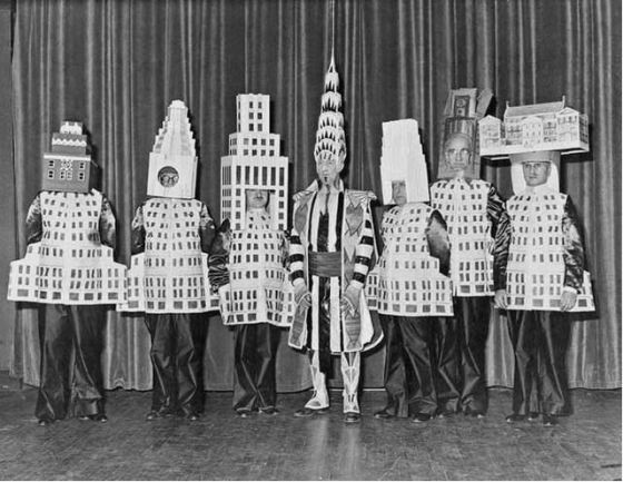 William Van Alen as the Chrysler Building, with other masquerading architects around him. On the far right is Joseph Freelander as the Museum of the City of New York.  Source: NY Times/untappedcities.com.