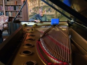 Hugh Gulledge patiently tunes the 1929 Steinway & Sons Model D Concert Grand in the West Wing Library of Cranbrook House. Photographer: Gretchen Sawatzki