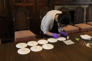 Desai, applying removable adhesive on Booths' saucers to attach inventory numbers.