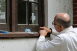 Ron Koenig, the owner of Building Arts & Conservation, takes samples of paint on the window frame at Tower Cottage.