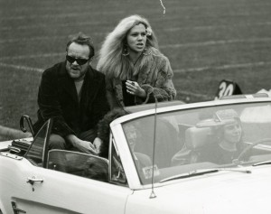 Homecoming Queen Barbara Tiso takes a convertible ride around the field with Academy President Wallace Mitchell.