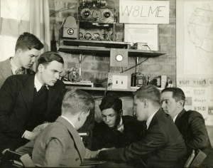 Boys sit around a ham radio.