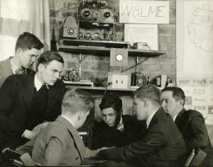 Boys sit around a ham radio.