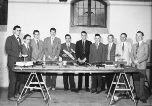 A group of boys standing behind a table of model airplanes