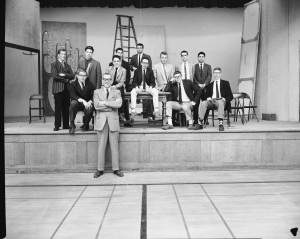 Group of boys sitting on a stage.
