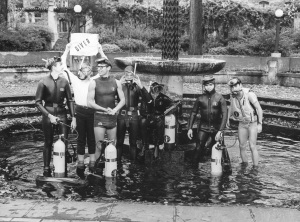 Group of boys in SCUBA gear standing in a fountain. of